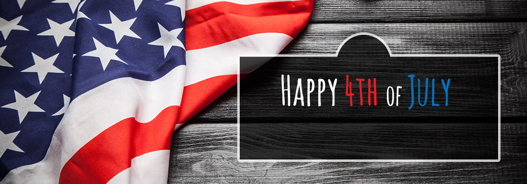 "Folded American flag on wood background with ""Happy 4th of July"" written"