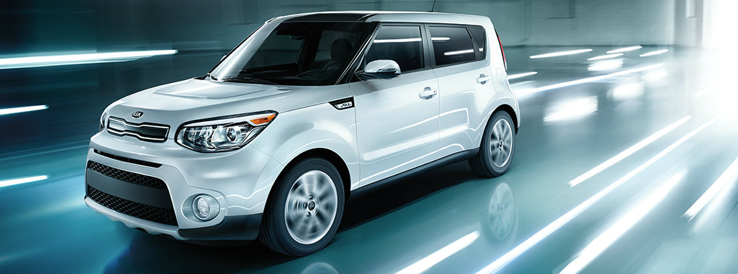 White 2018 Kia Soul driving on blue and white stylized background