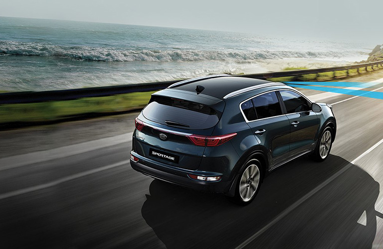 Rear view of 2018 Kia Sportage driving on empty road