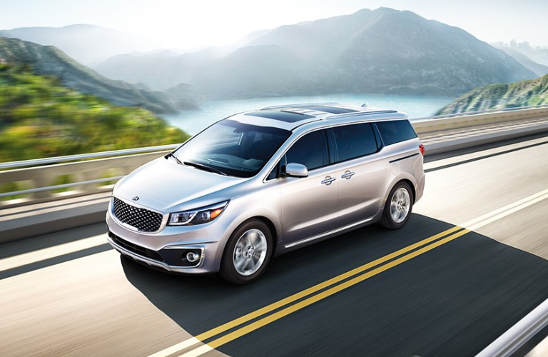 2018 Kia Sedona driving on road with mountainous landscape in background