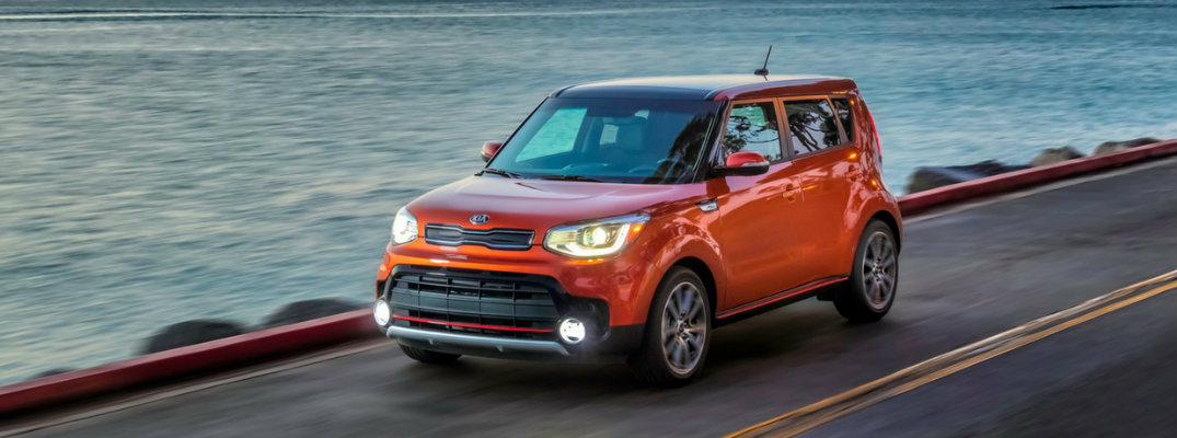 Orange 2019 Kia Soul driving on waterfront at sundown