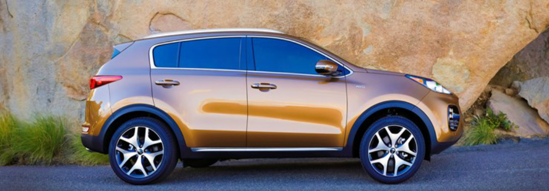 2019 Kia Sportage in gold parked in front of a rock formation