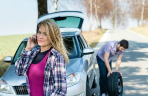 woman on phone while man changes tire