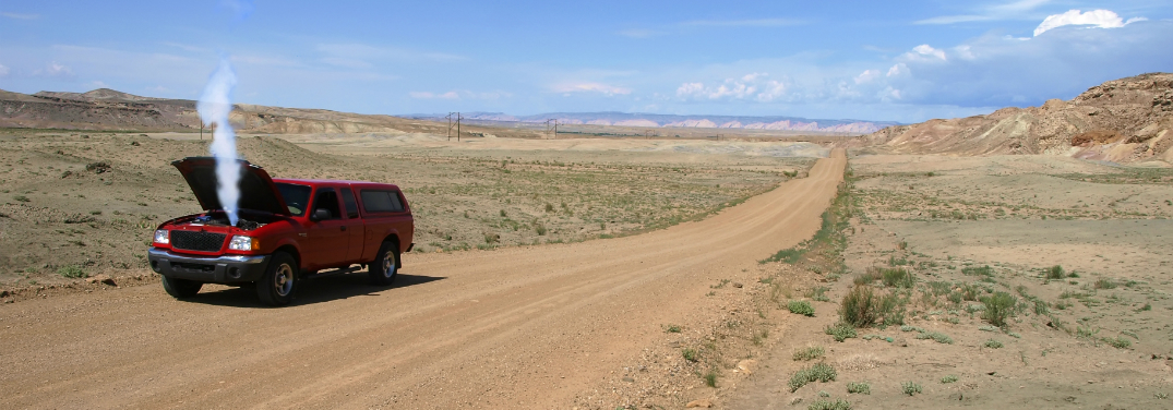 red truck broken down on desolate dirt road
