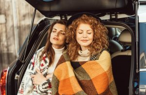 two women with blankets in back of vehicle