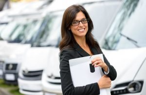 saleswoman holding keys and clipboard