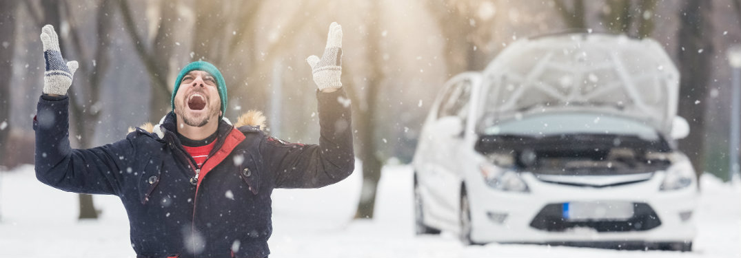 man screaming in snow with broken down car in background