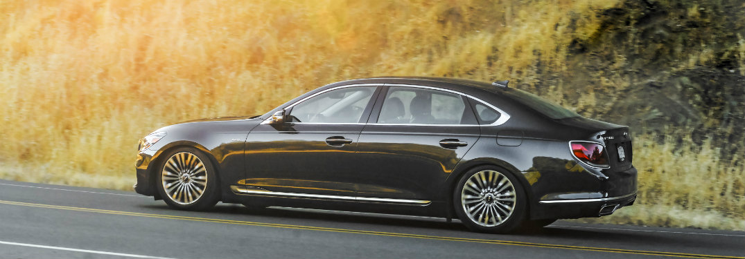 left side view of black kia k900 driving