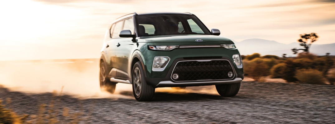 Exterior view of a Undercover Green 2020 Kia Soul driving down a dirt road