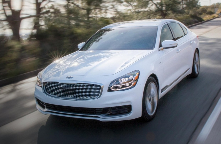 Exterior view of a white 2019 Kia K900 driving down a two-lane road