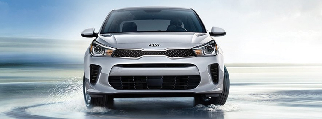 Exterior view of a silver 2019 Kia Rio driving on a wet surface