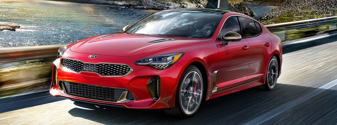 Exterior view of a red 2019 Kia Stinger driving over a bridge in the country