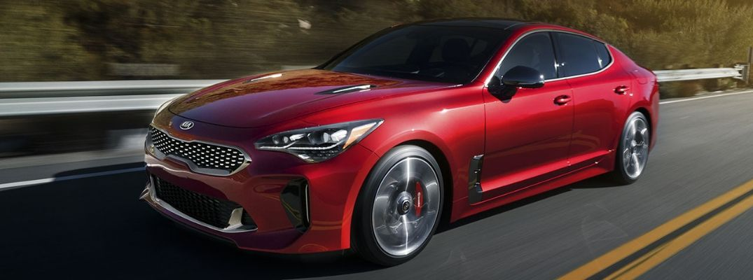 Exterior view of a HiChroma Red 2019 Kia Stinger driving down a two-lane row
