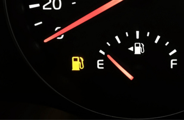 Closeup image of a vehicle's instrument cluster showing the Low Fuel Warning Light