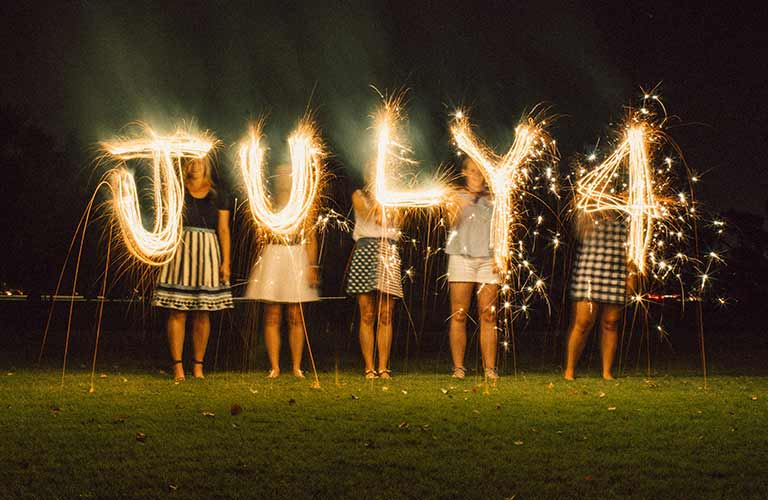 """Image of five kids spelling out """"July 4"""" with sparklers"""
