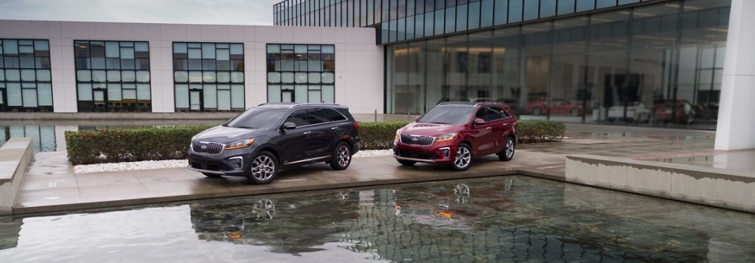Gray and Red 2020 Kia Sorento Models in Front of a Modern Building