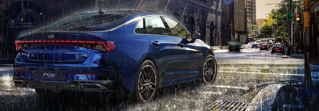 Blue 2021 Kia K5 Rear Exterior Driving on a City Street in Rain