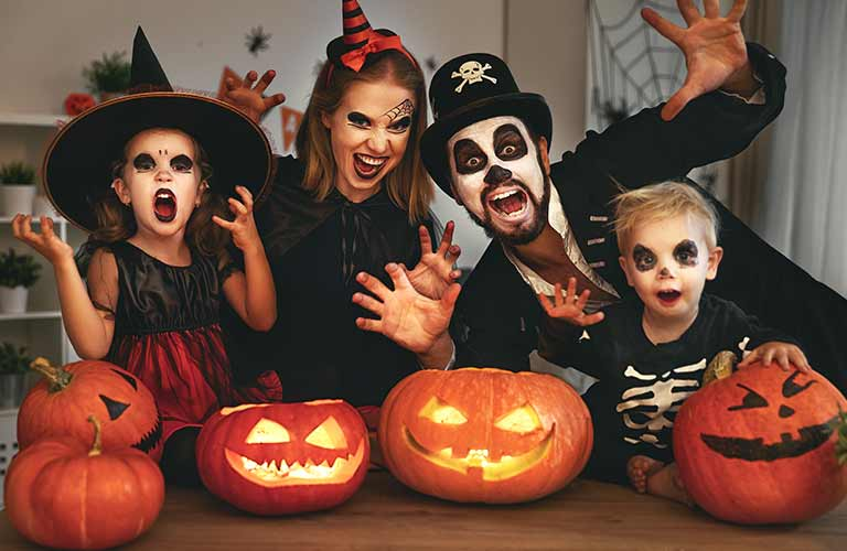 Family in Costumes with Jack-o-Lanterns at a Table