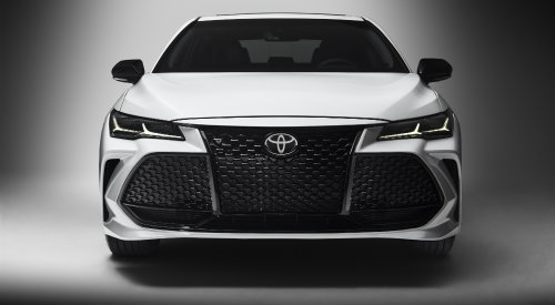 Shot of 2019 Toyota Avalon grille and headlights on silver background