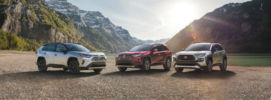 Three 2019 Toyota RAV4 models parked in front of mountainous landscape at sundown