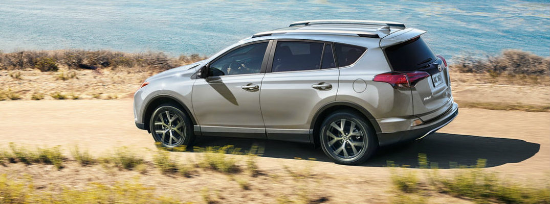Profile view of silver 2018 Toyota RAV4 driving on dirt waterfront road