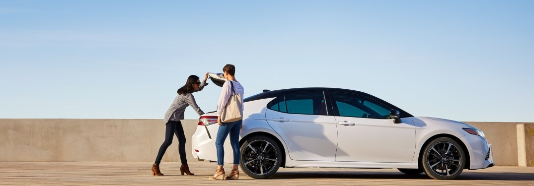 Two women opening up the trunk of a 2019 Toyota Camry