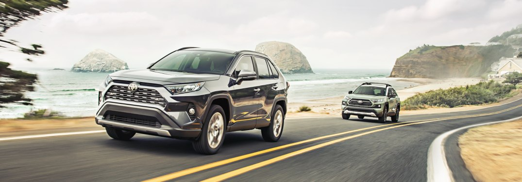 Two 2019 Toyota RAV4 models driving down a beachside road
