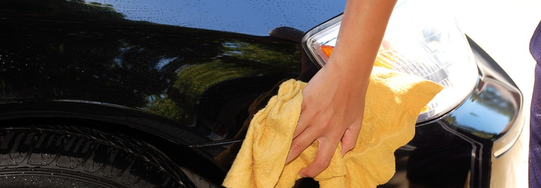 person cleaning vehicle with yellow towel