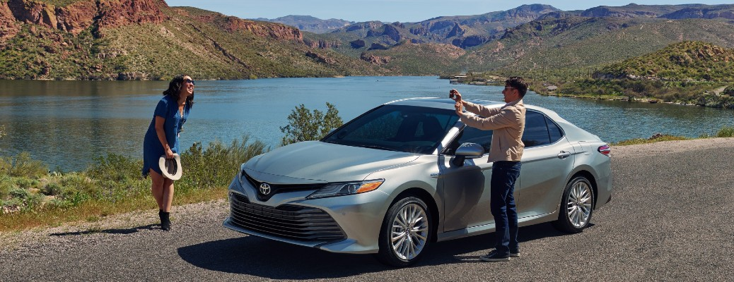 2020 Toyota Camry with couple taking photo near it
