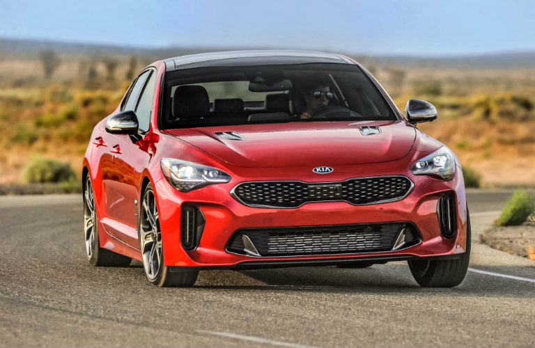 front view of red kia stinger in dessert