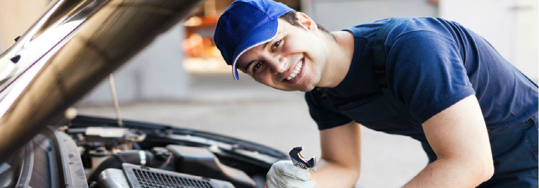 Mechanic working on a car with wrench in hand