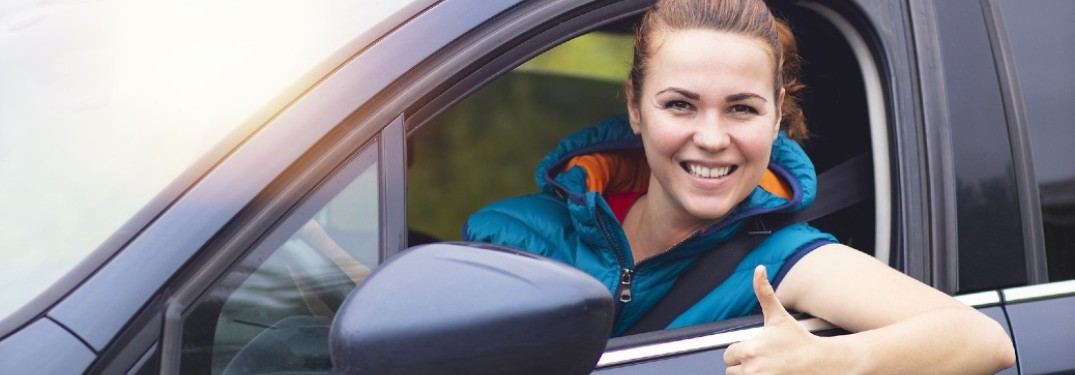 A woman in a vehicle smiling with her thumb up