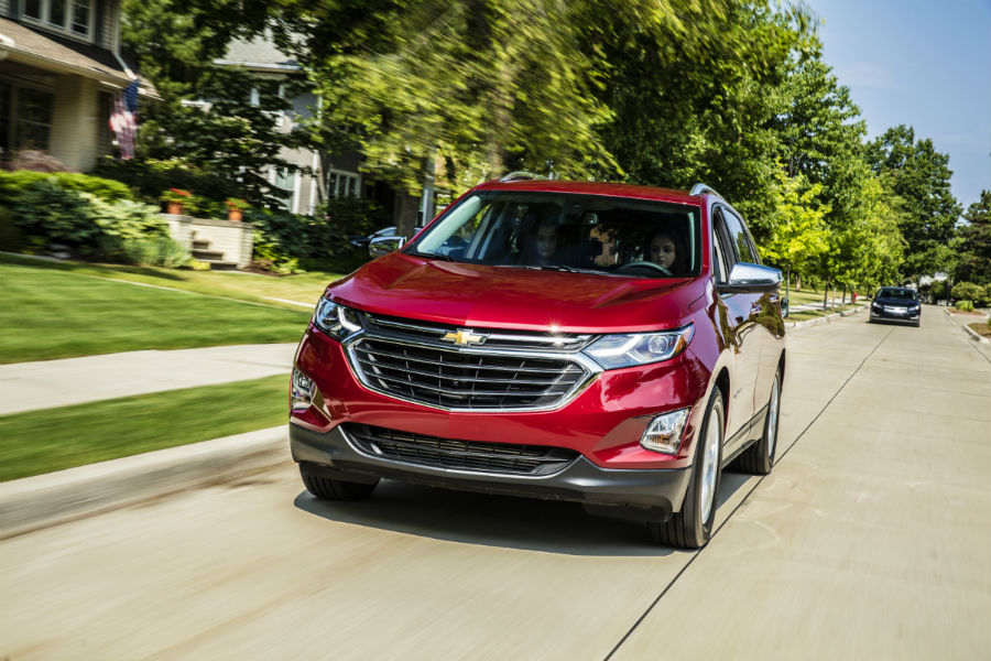 Front View Of A Red 2018 Chevy Equinox Driving Along A Residential Street