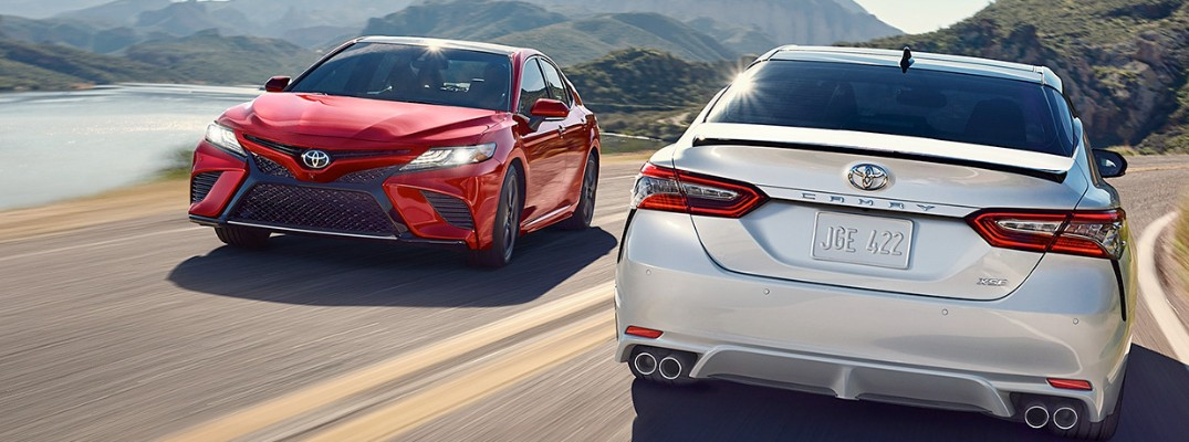 Two 2019 Toyota Camry models driving on waterfront road