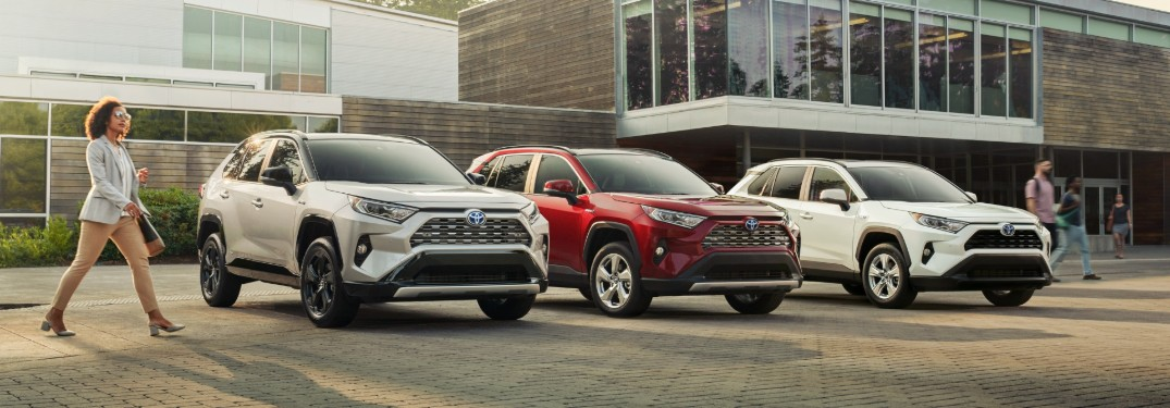 Three different colored 2019 Toyota RAV4 vehicles parked next to each other in front of a building with a woman walking towards them