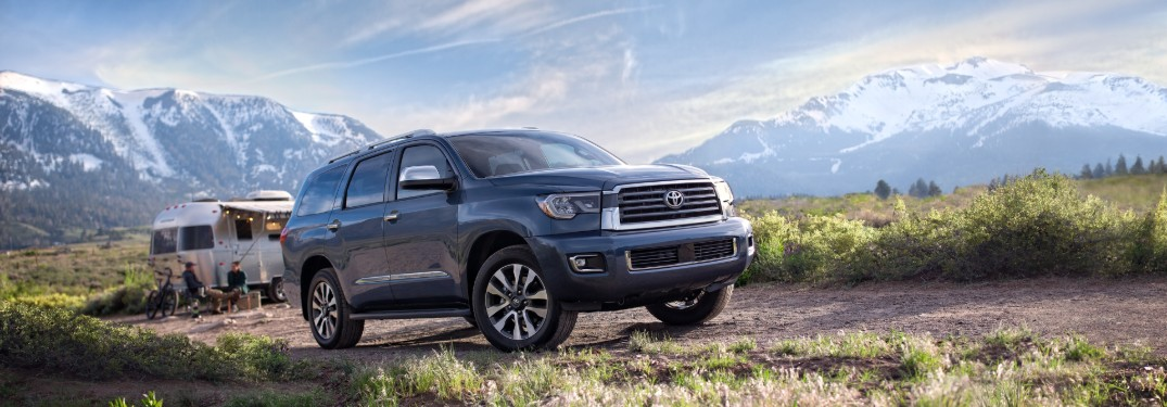 Front passenger angle of the 2020 Toyota Sequoia parked outdoors with a family camping behind it