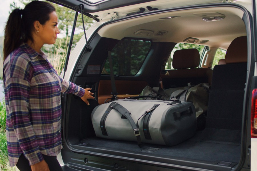 Rear view of the liftgate of the 2020 Toyota Sequoia open with bags inside and a woman pressing a button inside