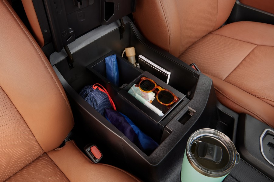 Close up of the storage area between the front row seats with belongings inside the 2020 Toyota Sequoia