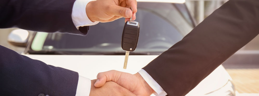 A stock photo of a sales person handing a set of keys to another person.