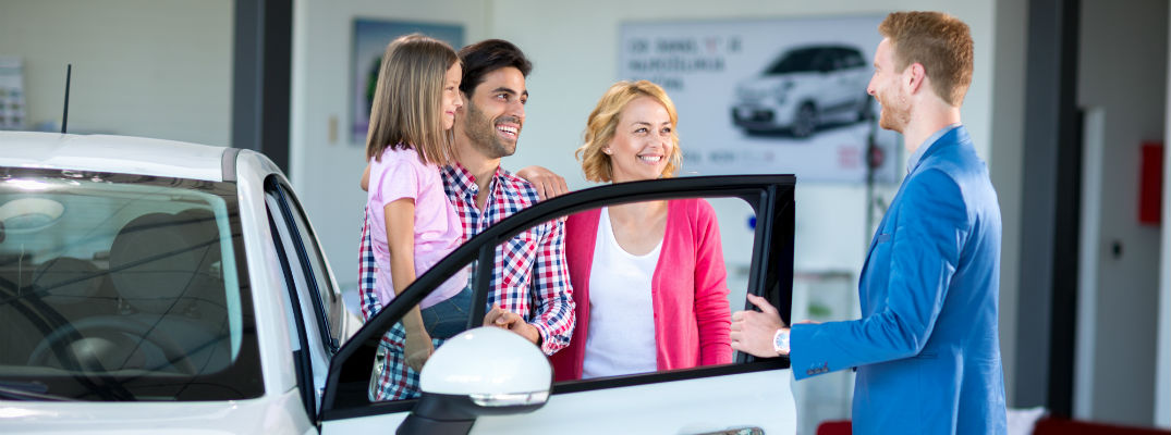 A stock photo of a family buying a new car.