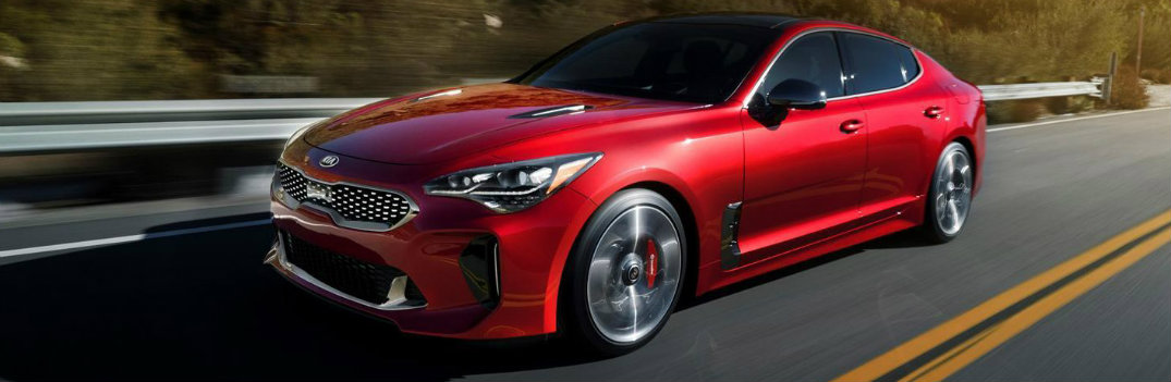 Red 2019 Kia Stinger driving fast down road
