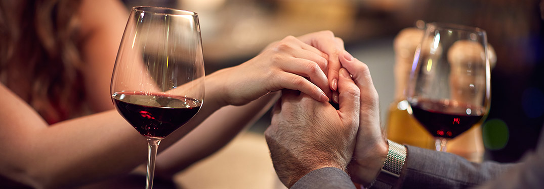 couple clasping hands next to a wine glass