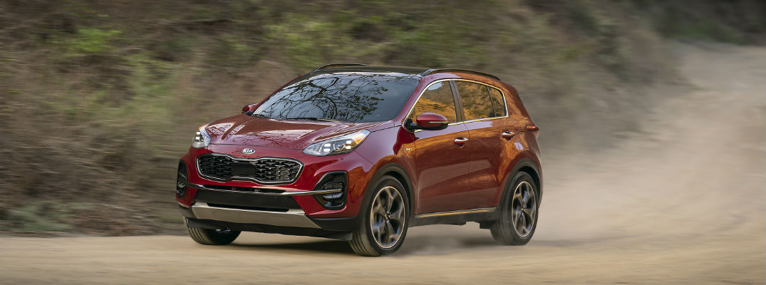 A front left quarter photo of the 2020 Kia Sportage driving on a dirt road.