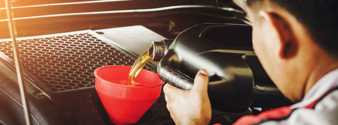 A stock photo of a person pouring oil into an engine.