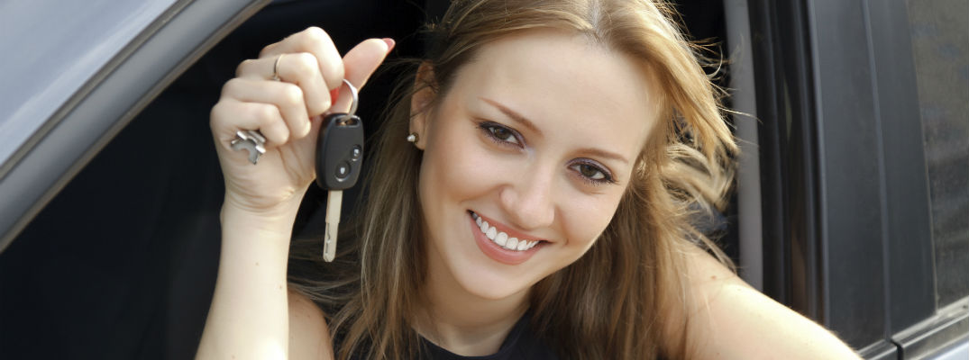 A stock photo of a young woman holding a set of car keys.