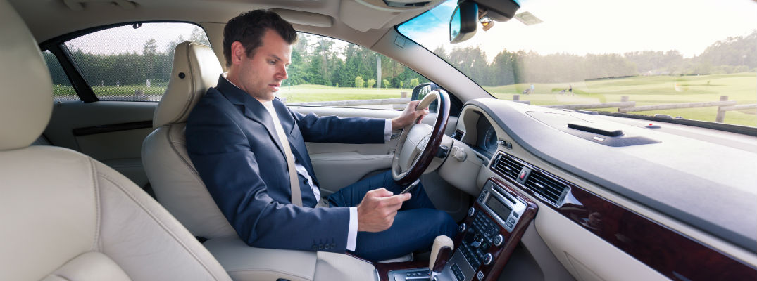 A stock photo of a man using a phone while driving.
