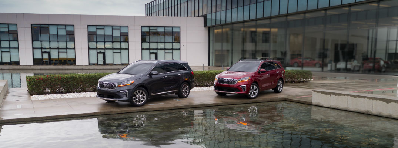 A photo of the two 2020 Kia Sorento parked by a Kia facility.