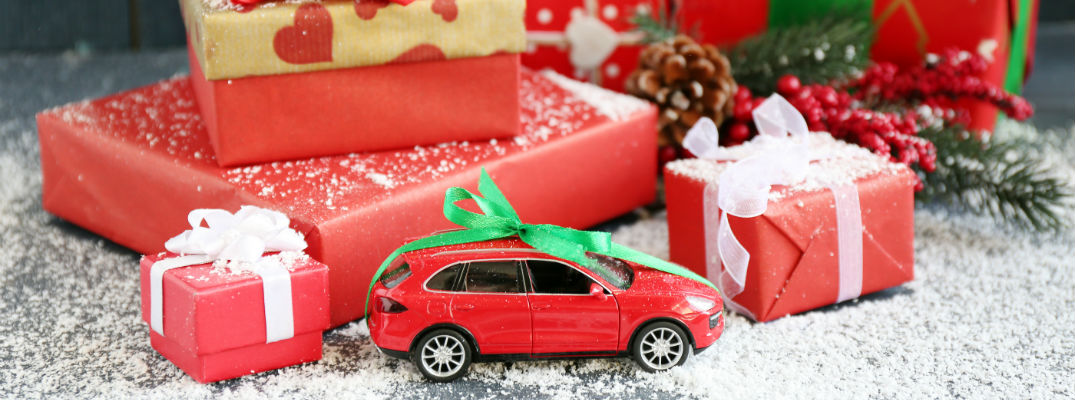 A stock photo of the a toy car in front of a stack of gifts.