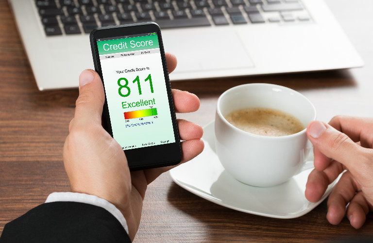 hand holding a cell phone showing excellent credit score of 811 with coffee mug in background