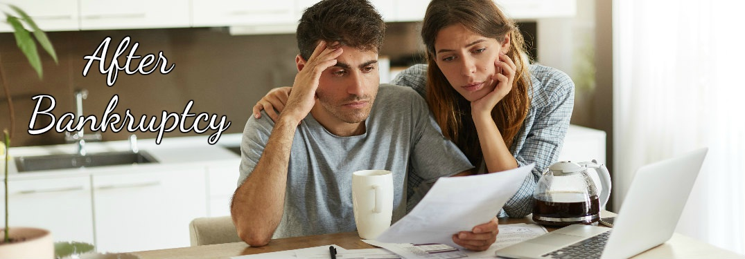 unhappy couple looking over finances in kitchen with overlaid text that reads after bankruptcy